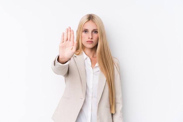 Jeune femme blonde d'affaires sur le mur blanc debout avec la main tendue montrant le panneau d'arrêt, vous empêchant.