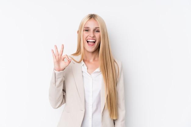 Jeune femme blonde d'affaires sur le mur blanc fait un clin d'œil et détient un geste correct avec la main.