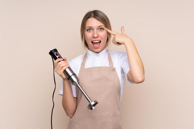 Jeune femme blonde à l'aide d'un mélangeur à main ayant l'intention de réaliser la solution