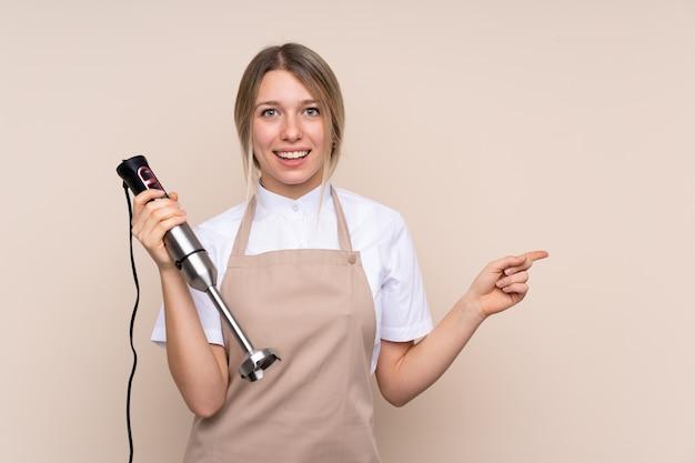 Jeune femme blonde à l'aide d'un mixeur plongeant surpris et pointant le doigt sur le côté