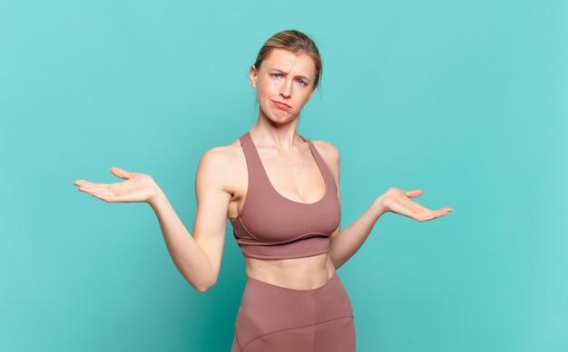 Jeune femme blonde à l'air perplexe, confuse et stressée, se demandant entre différentes options, se sentant incertaine. notion de sport