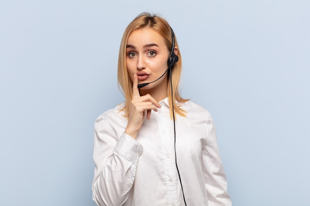 Jeune femme blonde à l'air sérieuse et croisée avec le doigt pressé sur les lèvres exigeant le silence ou le silence, gardant un secret