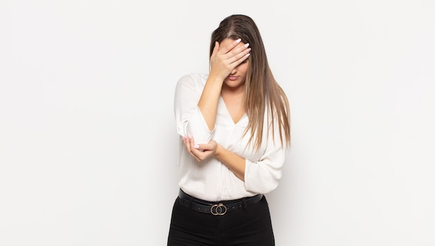 Jeune femme blonde à l'air stressée, honteuse ou contrariée, avec un mal de tête, couvrant le visage avec la main