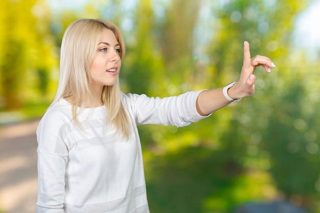 Jeune femme blonde en appuyant sur le bouton de l'écran tactile