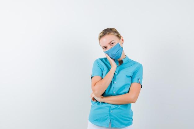 Jeune femme blonde appuyée sur la joue de la paume dans des vêtements décontractés, un masque et l'air fatigué