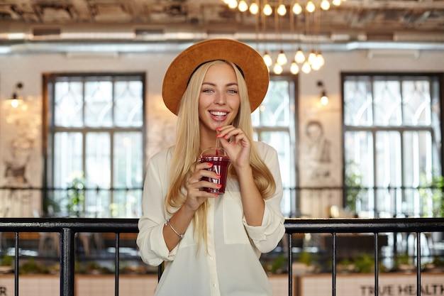Jeune femme blonde assez heureuse aux cheveux longs portant des vêtements à la mode et chapeau large, boire de la limonade avec de la paille tout en souriant joyeusement
