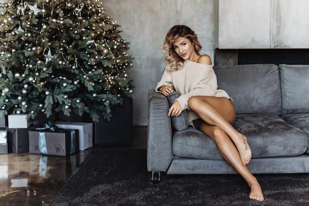 Jeune femme blonde assise sur un canapé