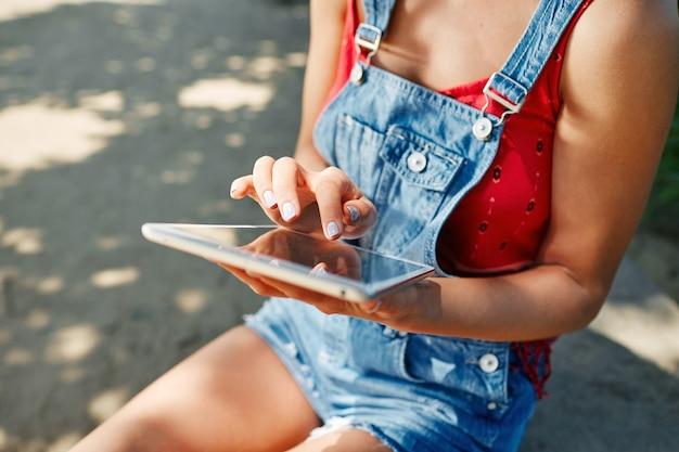 Jeune femme blonde assise dans le parc et à l'aide de tablette