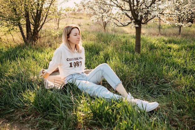 Jeune femme blonde assise sur l'herbe dans le parc à la lumière du soleil