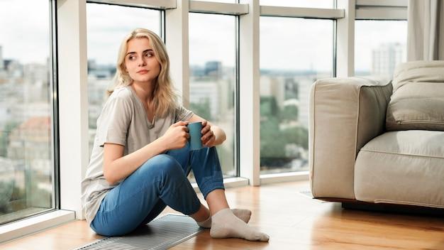 Jeune femme blonde assise sur le sol près de la fenêtre panoramique, avec une tasse