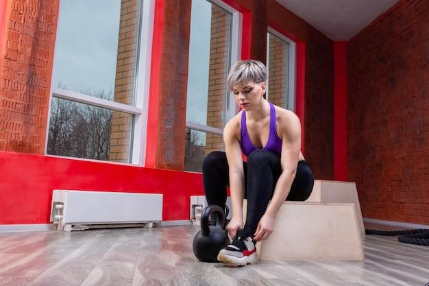 Une jeune femme blonde athlétique et heureuse posant avec des haltères dans une salle de sport