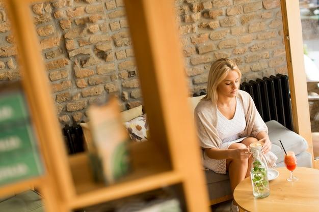 Jeune femme blonde au café