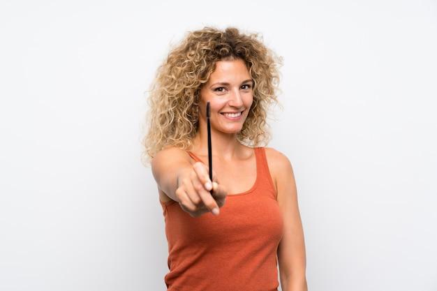 Jeune femme blonde aux cheveux bouclés, application de mascara à la ruée cosmétique