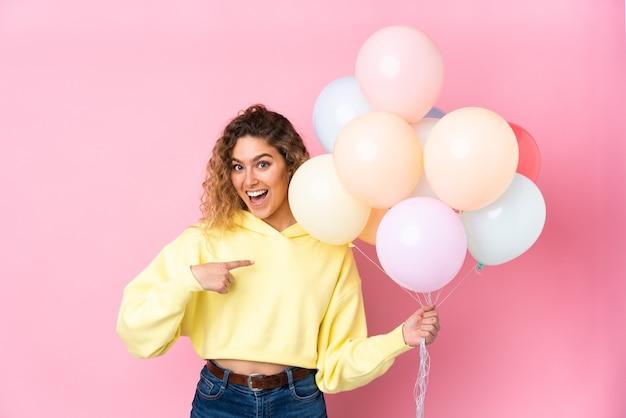 Jeune femme blonde aux cheveux bouclés attraper de nombreux ballons isolés sur un mur rose avec une expression faciale surprise