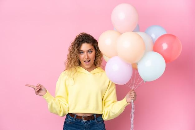Jeune femme blonde aux cheveux bouclés attraper de nombreux ballons isolés sur un mur rose surpris et pointant le doigt sur le côté