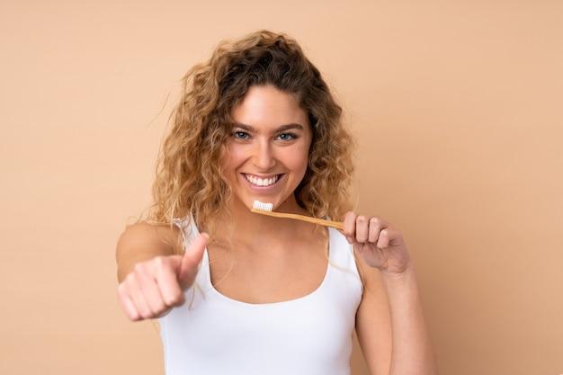 Jeune femme blonde aux cheveux bouclés isolé sur beige avec une brosse à dents