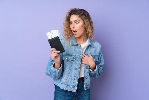 Jeune femme blonde aux cheveux bouclés isolé sur mur violet en vacances avec des billets d'avion et surpris