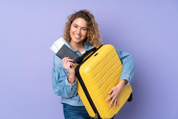 Jeune femme blonde aux cheveux bouclés isolé sur mur violet en vacances avec valise et passeport
