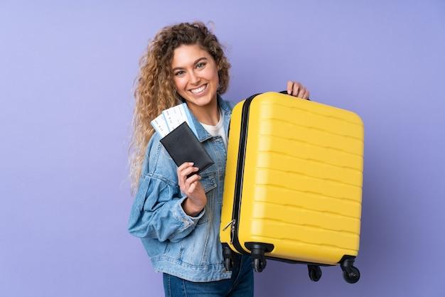 Jeune femme blonde aux cheveux bouclés isolé sur violet en vacances avec valise et passeport