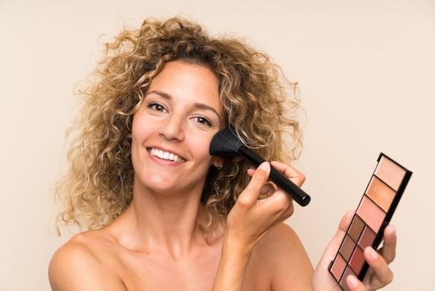 Jeune femme blonde aux cheveux bouclés avec un pinceau de maquillage