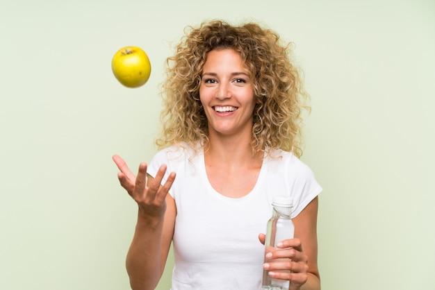 Jeune femme blonde aux cheveux bouclés avec une pomme et avec une bouteille d'eau