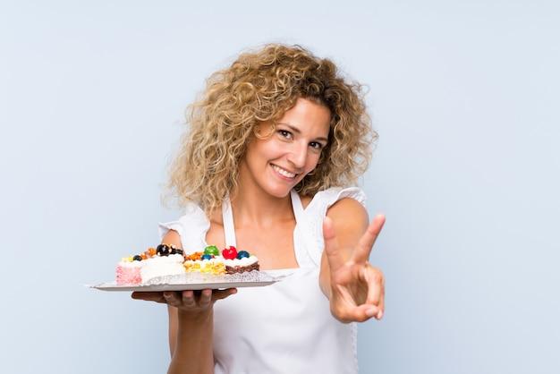 Jeune femme blonde aux cheveux bouclés tenant beaucoup de mini gâteaux différents
