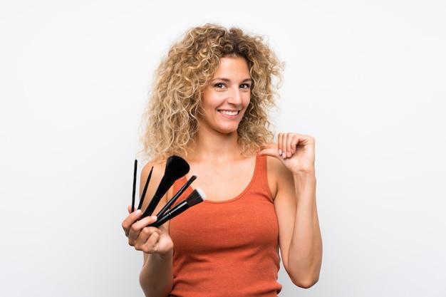 Jeune femme blonde aux cheveux bouclés tenant beaucoup de pinceau à maquillage fier et satisfait