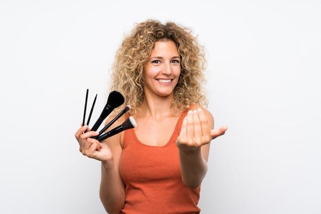 Jeune femme blonde aux cheveux bouclés tenant beaucoup de pinceau à maquillage invitant à venir avec la main. heureux que tu sois venu