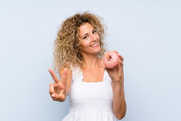 Jeune femme blonde aux cheveux bouclés tenant un beignet sur un mur bleu isolé, souriant et montrant le signe de la victoire