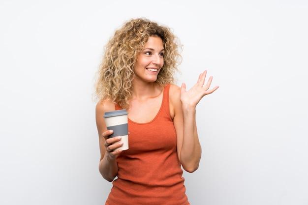Jeune femme blonde aux cheveux bouclés tenant un café à emporter avec une expression faciale surprise