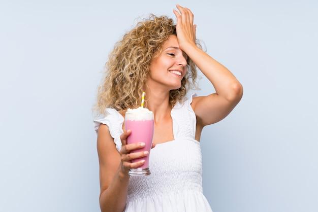 Jeune femme blonde aux cheveux bouclés tenant un milkshake à la fraise a réalisé quelque chose et dans l'intention de la solution