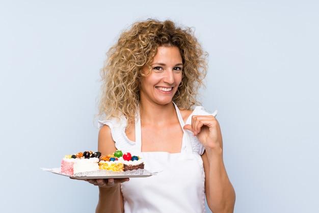 Jeune femme blonde aux cheveux bouclés tenant plein de mini gâteaux différents fiers et satisfaits