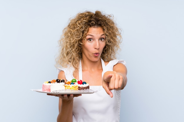Jeune femme blonde aux cheveux bouclés tenant plein de mini gâteaux différents surpris et pointant devant