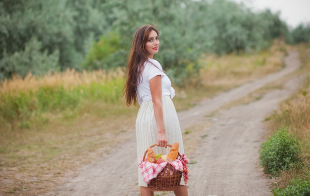 Jeune femme blonde aux cheveux longs dans des vêtements vintage de style rétro avec panier de pique-nique marchant sur l'atterrissage