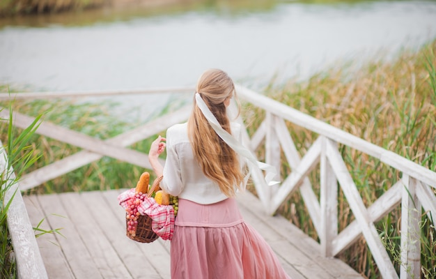 Jeune femme blonde aux cheveux longs dans des vêtements vintage de style rétro se dresse avec un panier de pique-nique sur une jetée en bois du lac
