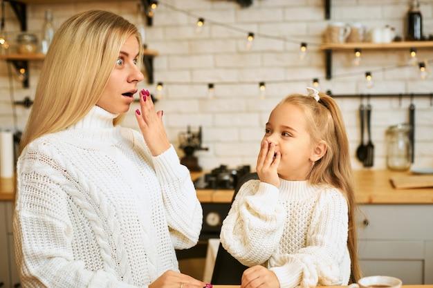 Jeune femme blonde aux cheveux longs étonnée et sa jolie petite fille posant dans un intérieur de cuisine élégant avec guirlande, ayant surpris des regards choqués, couvrant la bouche, exprimant de vraies émotions