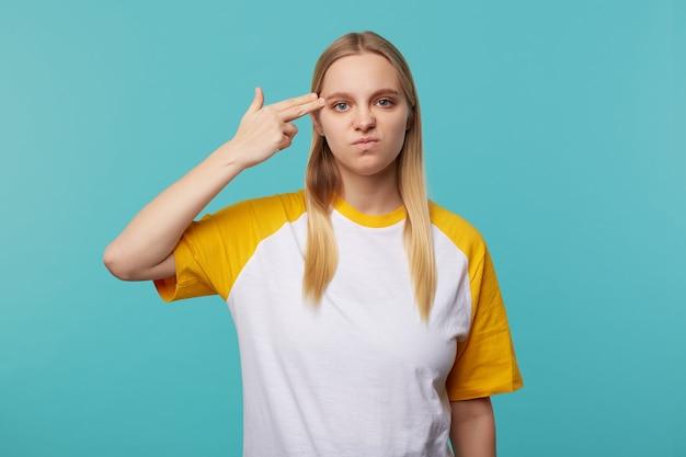 Jeune femme blonde aux cheveux longs mécontent pliant le pistolet avec la main levée et le garder sur la tempe tout en regardant la caméra avec la moue, isolé sur fond bleu