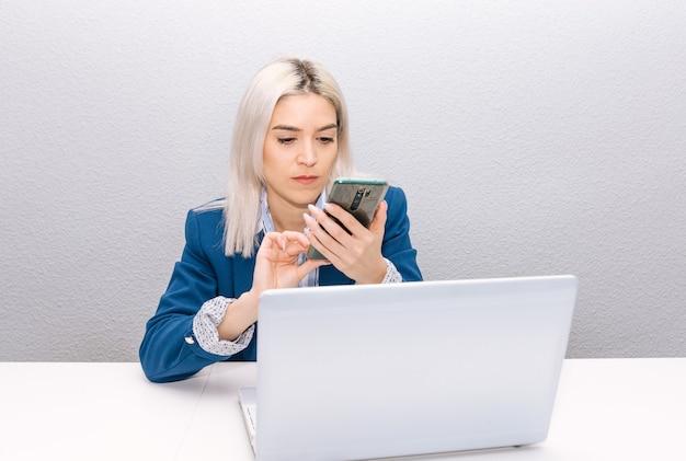 Jeune femme blonde aux cheveux platine vêtue d'un blazer bleu télétravail à domicile avec téléphone et ordinateur portable. concept de télétravail.