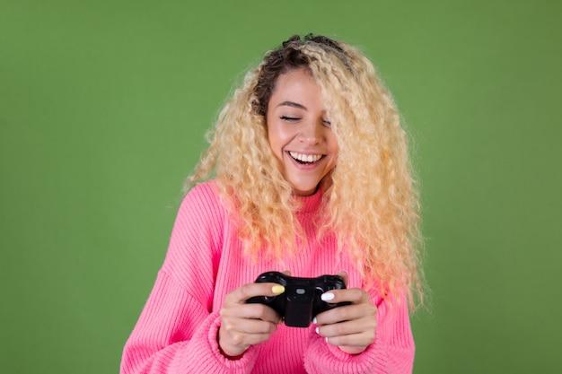 Jeune femme blonde aux longs cheveux bouclés en pull rose sur vert avec joystick jouant à des jeux