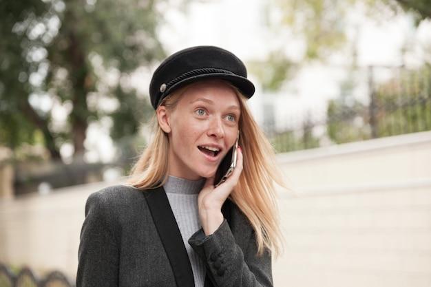 Jeune femme blonde aux yeux ouverts à la mode dans un chapeau noir faisant appel tout en marchant en plein air, regardant vers l'avant avec un visage surpris tout en entendant des nouvelles inattendues
