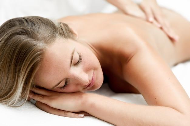 Jeune femme blonde ayant un massage dans le salon de spa