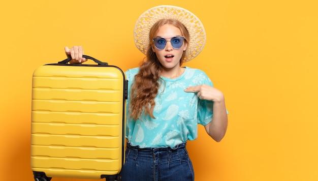 Jeune femme blonde avec des bagages jaunes