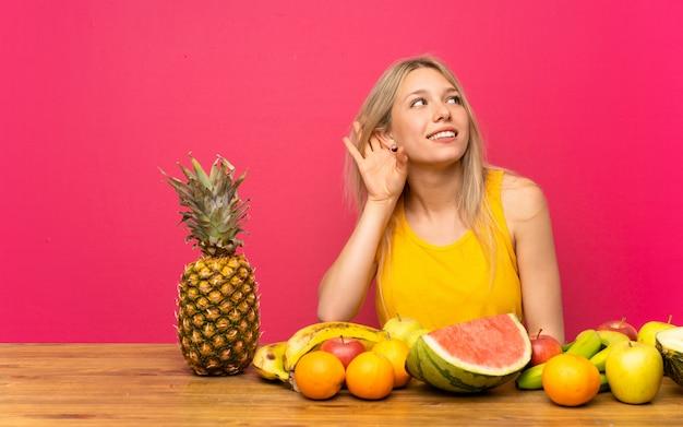 Jeune femme blonde avec beaucoup de fruits écoute quelque chose