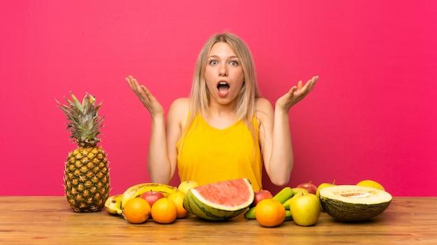 Jeune femme blonde avec beaucoup de fruits avec une expression faciale surprise