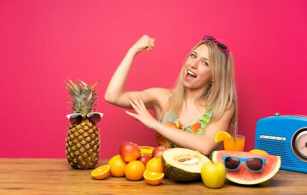 Jeune femme blonde avec beaucoup de fruits faisant un geste fort