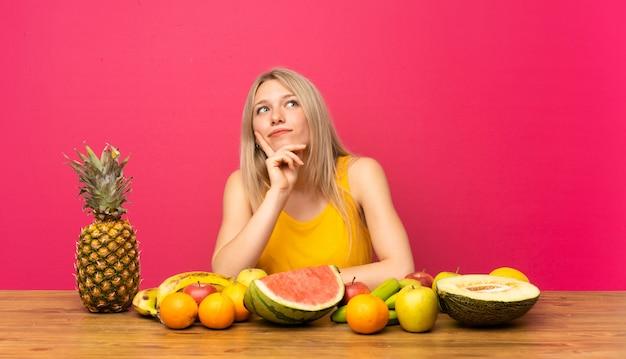 Jeune femme blonde avec beaucoup de fruits pense à une idée
