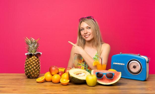 Jeune femme blonde avec beaucoup de fruits, pointant le doigt sur le côté
