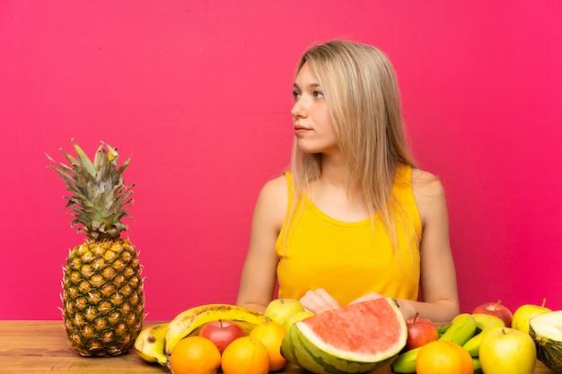 Jeune femme blonde avec beaucoup de fruits à la recherche de côté