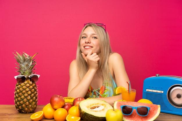 Jeune femme blonde avec beaucoup de fruits en riant