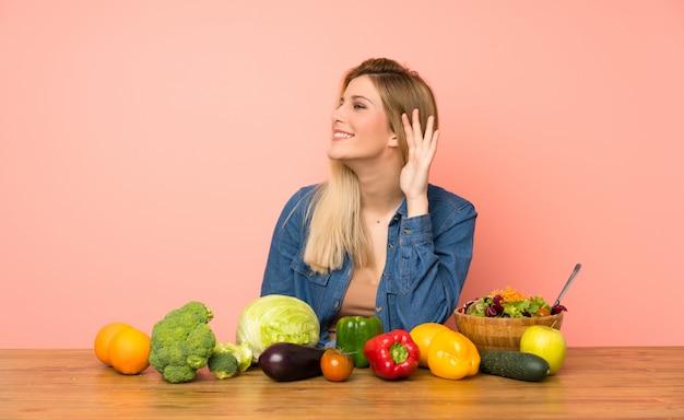 Jeune femme blonde avec beaucoup de légumes écouter quelque chose en mettant la main sur l'oreille